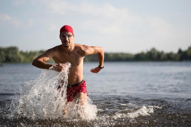 Medio geschoten zwemmer die in meer loopt