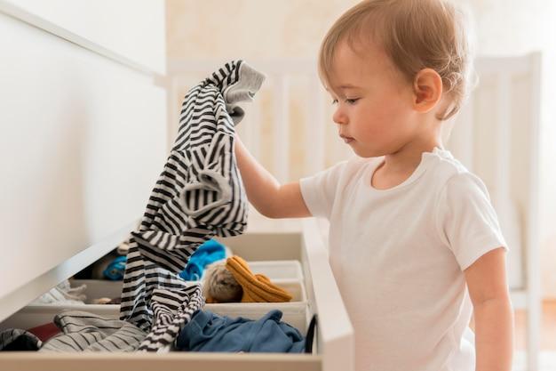 Medio geschotene baby die kleren van lade neemt