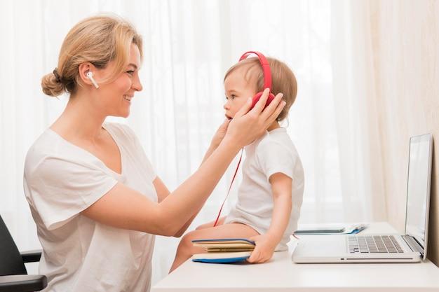 Medio geschotene baby op bureau met hoofdtelefoons en moeder