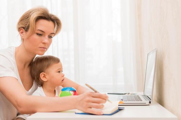 Medio geschotene de baby die van de vrouwenholding bij bureau werkt
