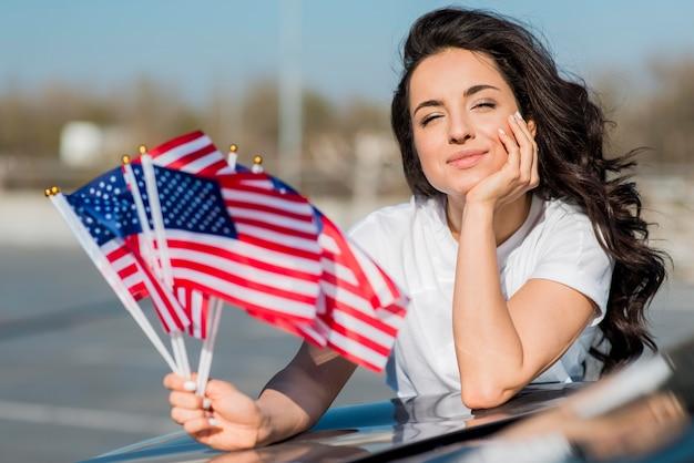 Medio geschotene donkerbruine vlaggen van de vs van de vrouwenholding op auto