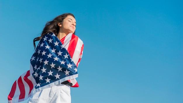 Medio geschotene donkerbruine vrouw die de grote vlag van de vs en het glimlachen houdt