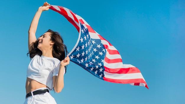 Medio geschotene jonge donkerbruine vrouw die de grote vlag van de vs houdt