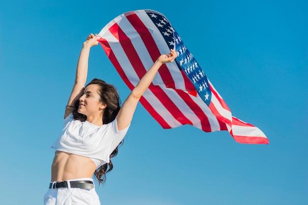 Medio geschotene jonge glimlachende vrouw die de grote vlag van de vs houdt