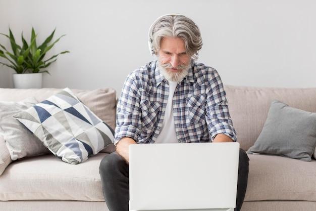 Medio geschotene leraar die aan laptop werkt
