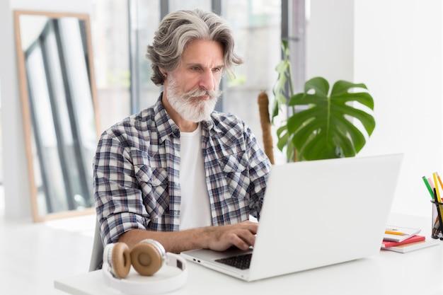 Medio geschotene leraar die bij bureau blijft dat laptop met behulp van
