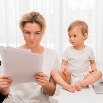 Medio geschotene moeder die in documenten en baby op bureau kijkt