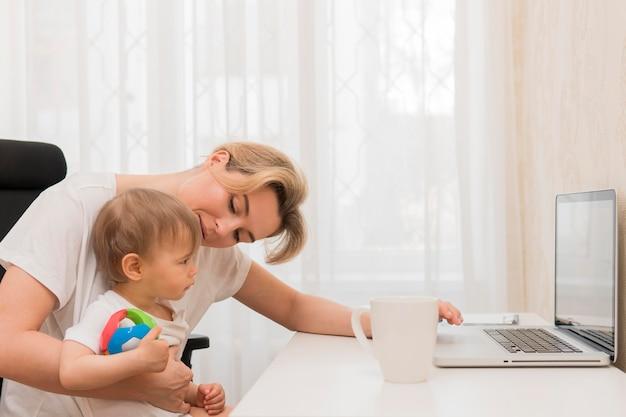 Medio geschotene moeder en baby bij bureau