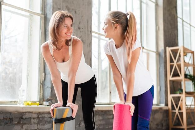 Medio geschotene moeder en dochter die yogamatten houden die elkaar bekijken