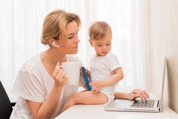 Medio geschotene moeder het drinken koffie en baby op bureau