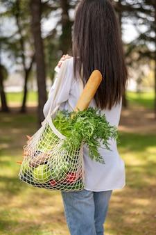 Medio geschotene vrouw die herbruikbare zak buiten houdt