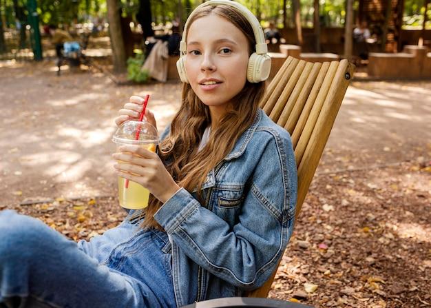 Medio ontsproten jonge vrouw die met hoofdtelefoons vers sap houdt