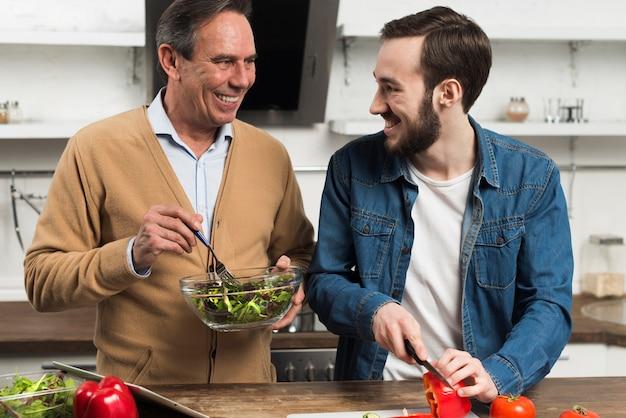 Medio schot gelukkige vader en zoon die salade in keuken maken