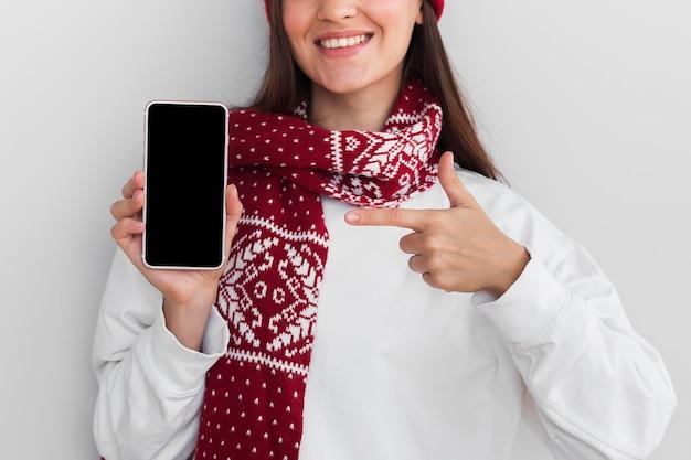 Medio schot glimlachende vrouw met de telefoon van de hoedenholding