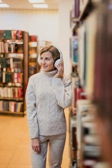 Medio schot glimlachende vrouw met hoofdtelefoons in boekhandel