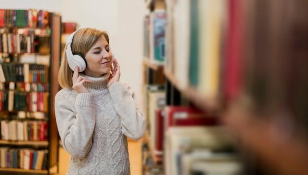 Medio schotvrouw met hoofdtelefoons in boekhandel