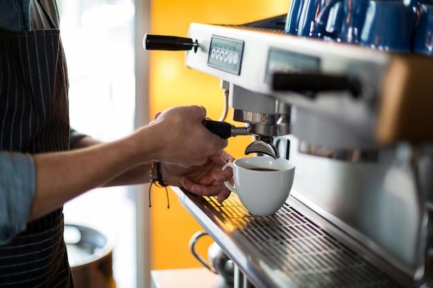 Medio sectie die van ober kop van koffie maken bij teller