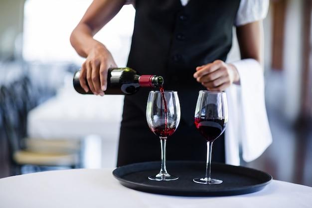 Medio sectie die van serveerster rode wijn in een glas gieten