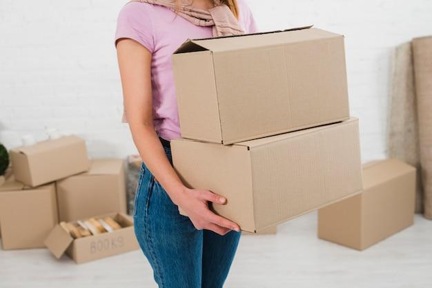 Medio sectie over een jonge vrouw met stapel kartonnen dozen