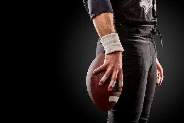 Medio sectie van amerikaanse voetbalster met bal tegen zwarte, exemplaarruimte, zijaanzicht