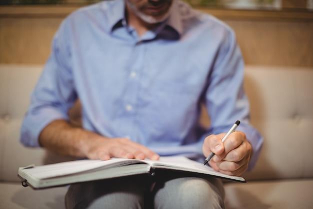 Medio sectie van arts die in organisator schrijft