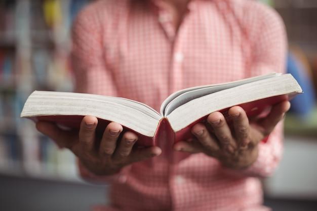Medio sectie van de holdingsboek van de schoolleraar in bibliotheek