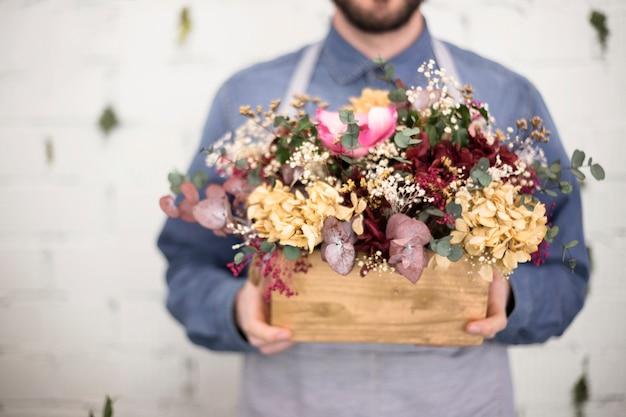 Medio sectie van de mens die houten krat met kleurrijke bloemen houdt