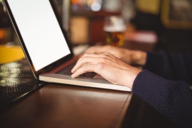 Medio sectie van de mens die laptop met behulp van