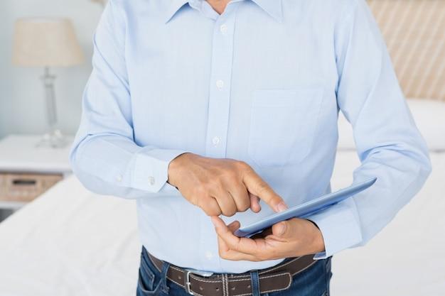 Medio sectie van de mens die tablet in slaapkamer gebruiken