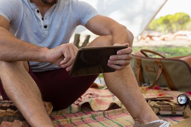 Medio sectie van de mens die tablet in tent gebruiken