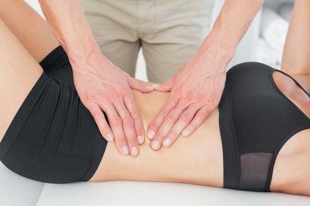 Medio sectie van een fysiotherapeut die het lichaam van de vrouw masseren