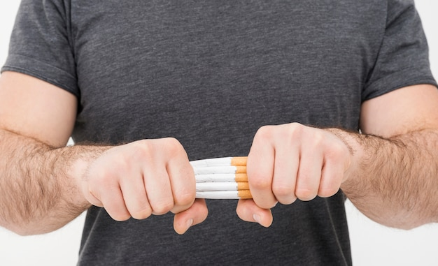 Medio sectie van een mens die de bundel van sigaretten met twee handen breekt