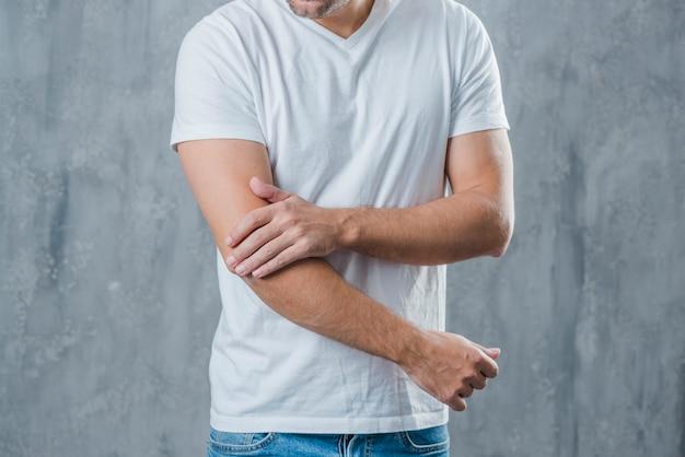 Medio sectie van een mens die elleboogpijn heeft die zich tegen grijze achtergrond bevindt