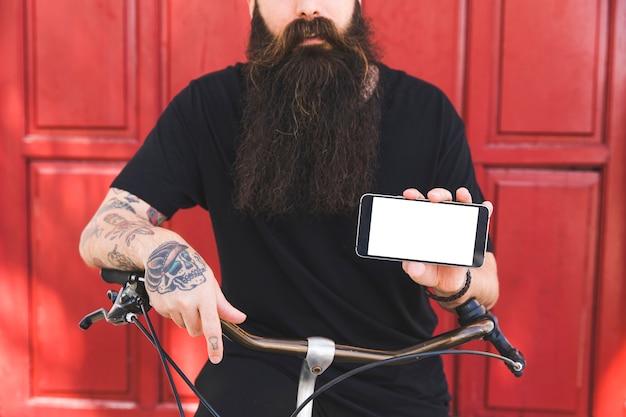 Medio sectie van een mens met tatoegering op zijn hand die mobiele telefoon in hand houdt