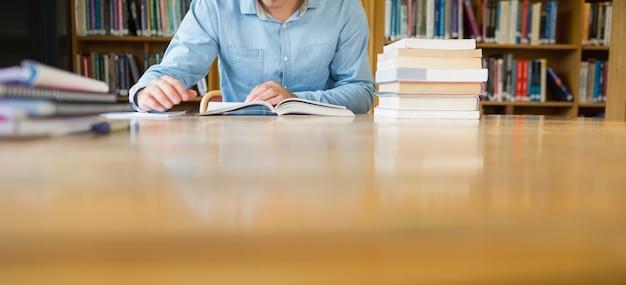 Medio sectie van een student die bij bibliotheekbureau bestudeert