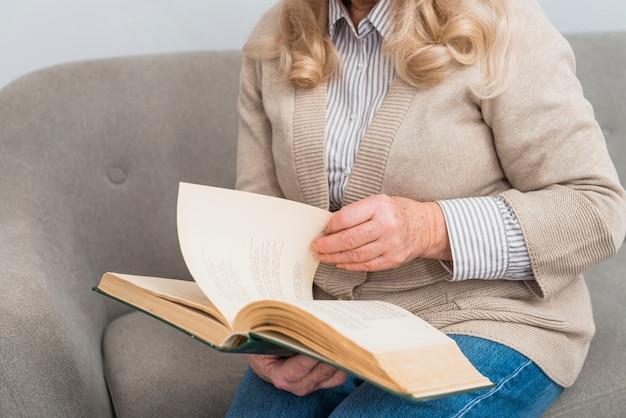 Medio sectie van een vrouw die de pagina's van boek draait