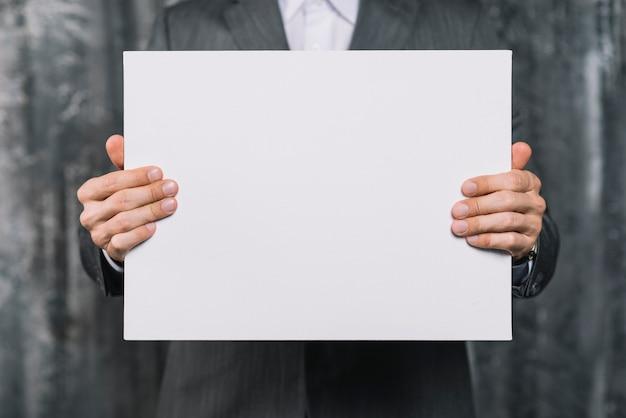 Medio sectie van een zakenman die leeg wit aanplakbiljet toont