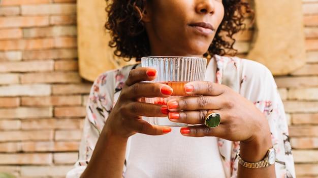 Medio sectie van het glas van de vrouwenholding sap in de hand