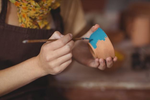 Medio sectie van het vrouwelijke pottenbakker schilderen op kom