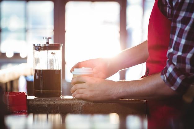 Medio sectie van kelner die koffie voorbereiden