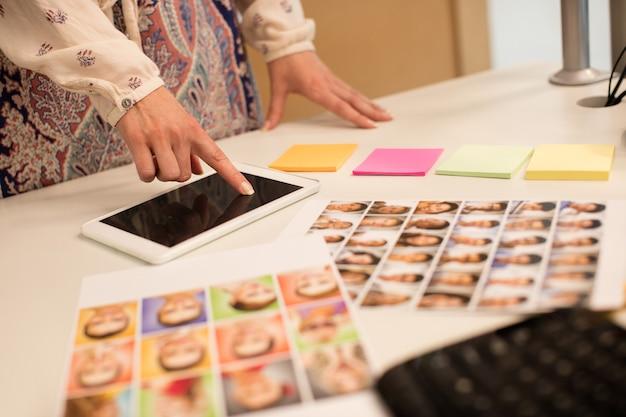 Medio sectie van onderneemster die aan digitale tablet werkt