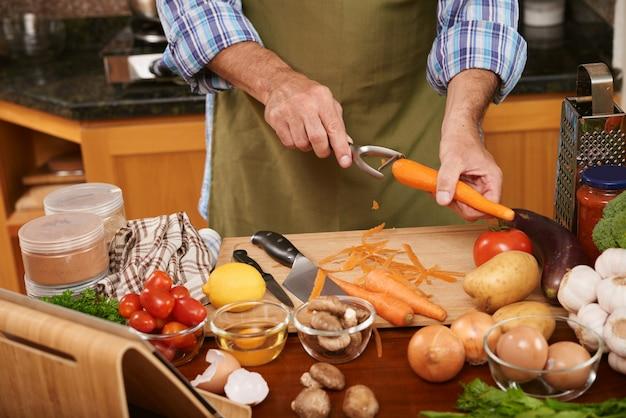 Medio sectie van onherkenbare kok die ingrediënten voor de schavende wortelen van de dinerschotel voorbereiden