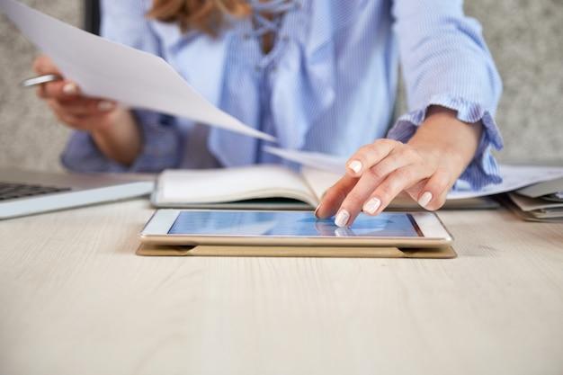 Medio sectie van onherkenbare vrouw die met tabletpc bij het bureau werkt