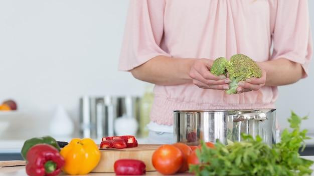 Medio sectie van vrouw die broccoli voorbereidt