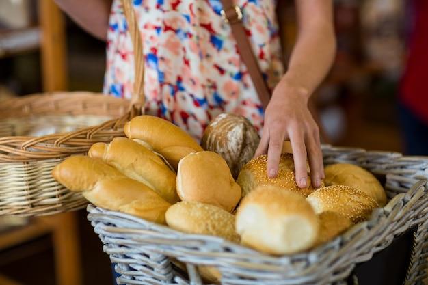 Medio sectie van vrouw die brood selecteert