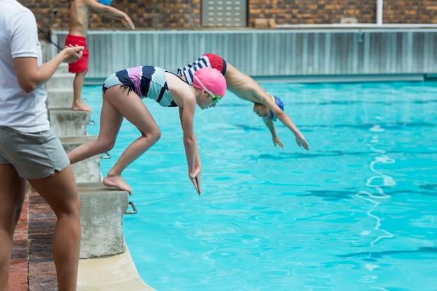 Medio sectie van vrouwelijke instructeur die de tijd van kinderen controleert die in pool duiken
