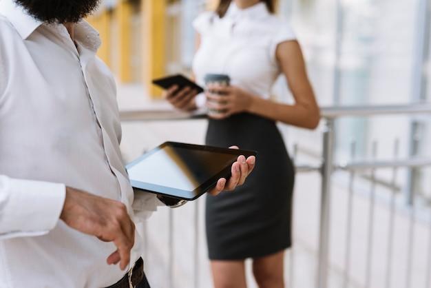 Medio sectie van zakenman die digitale tablet met onderneemster houdt die zich in de achtergrond bevindt