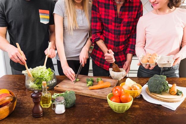 Medio sectie vrienden die voedsel in de keuken voorbereiden
