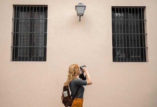 Medio shor vrouw die foto's met camera neemt