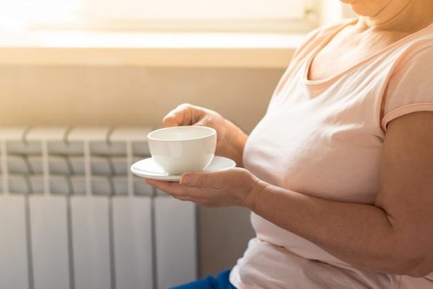 Medio volwassen vrouw het drinken koffie en het kijken uit het venster op zonnige dag. horizontale sha